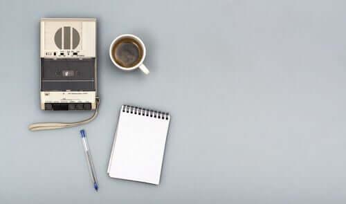 Gravador, café e caderno de anotações