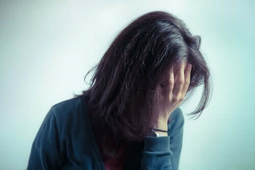 Mulher com ansiedade escondendo o rosto