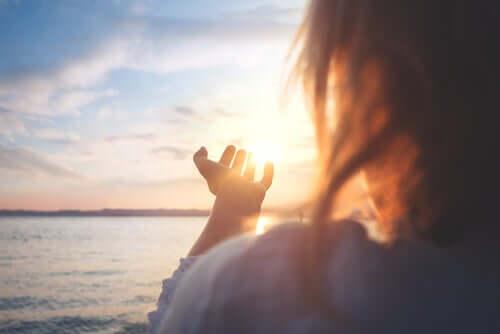 Mulher com as mãos para o céu