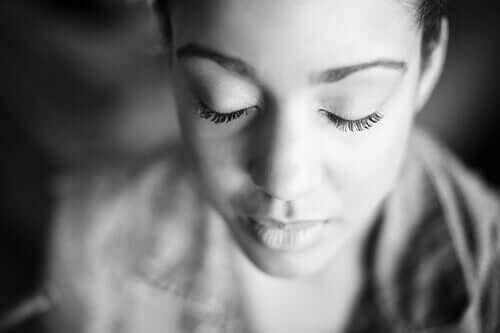 Mulher de olho fechados refletindo