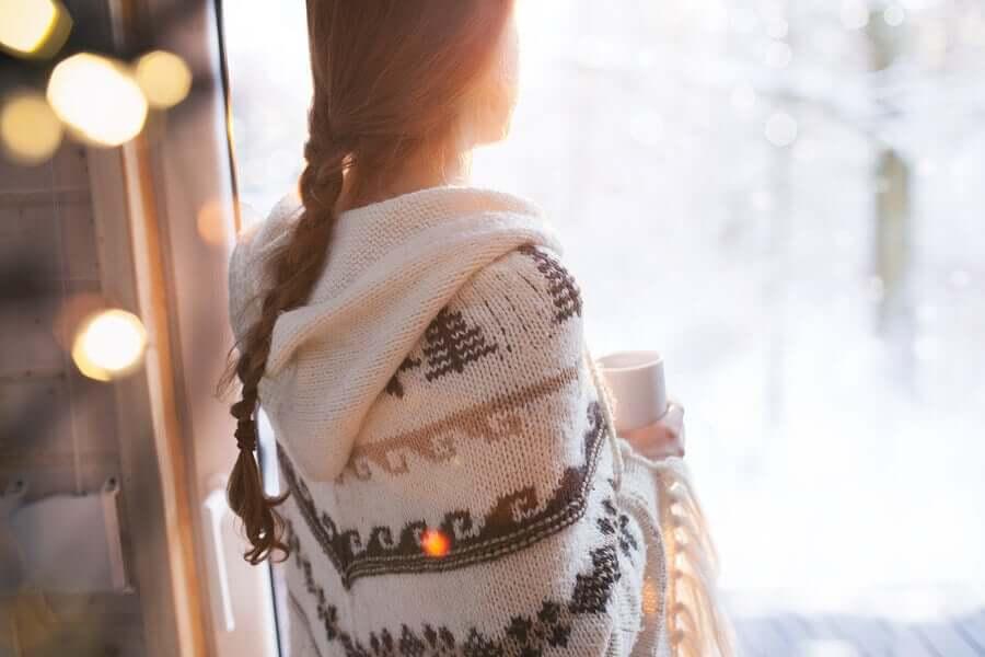 Mulher tomando xícara de café na janela