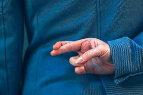 Pessoa cruzando os dedos ao mentir