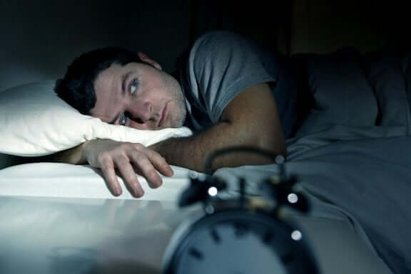 Homem com insônia sem conseguir dormir
