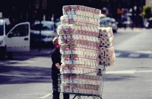 Pessoa comprando muitos pacotes de papel higiênico
