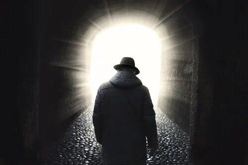 Homem caminhando em direção à luz