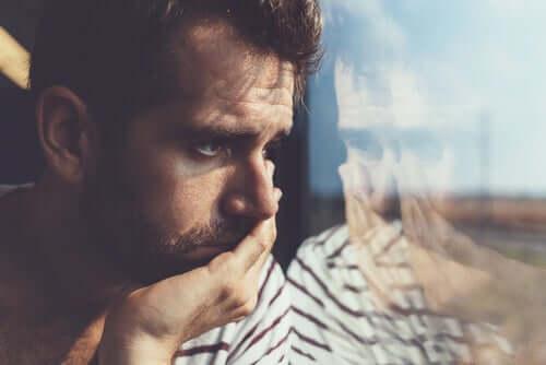 Homem chateado olhando pela janela