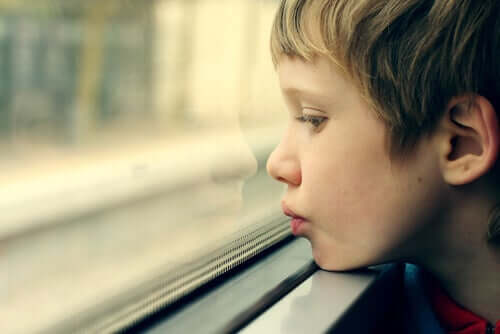 Menino chateado olhando pela janela