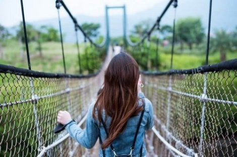 Mulher andando em ponte suspensa