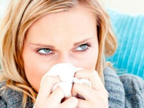 Mulher espirrando com lenço