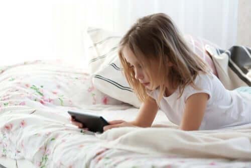 Menina com tablet na cama