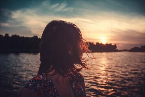 Mulher olhando para o por do sol e pensando em seu propósito de vida
