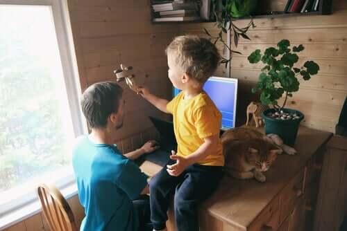 Pai trabalhando e filho brincando