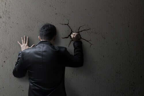 Homem dando um soco na parede