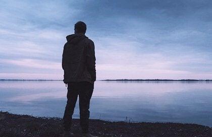 Homem observando um lago
