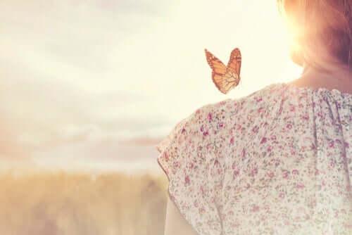 Mulher com borboleta no ombro