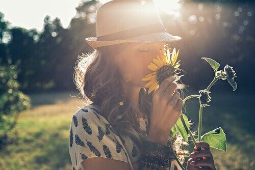 Mulher cheirando uma flor