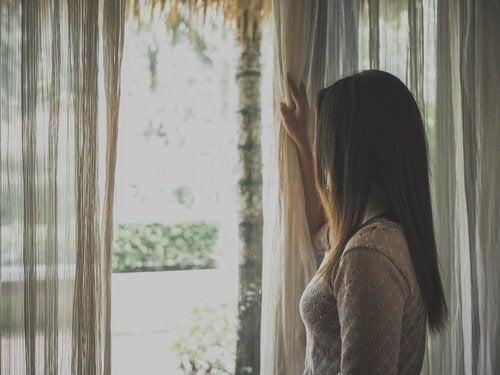 Mulher na janela durante a quarentena