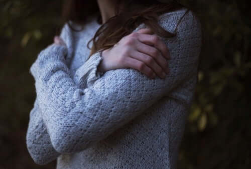 """Mulher se abraçando e pensando """"Eu não me amo"""""""