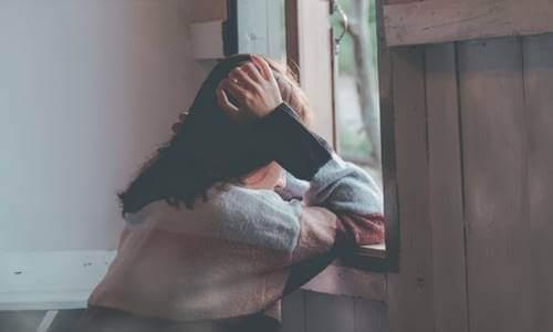 Mulher sentada diante da janela