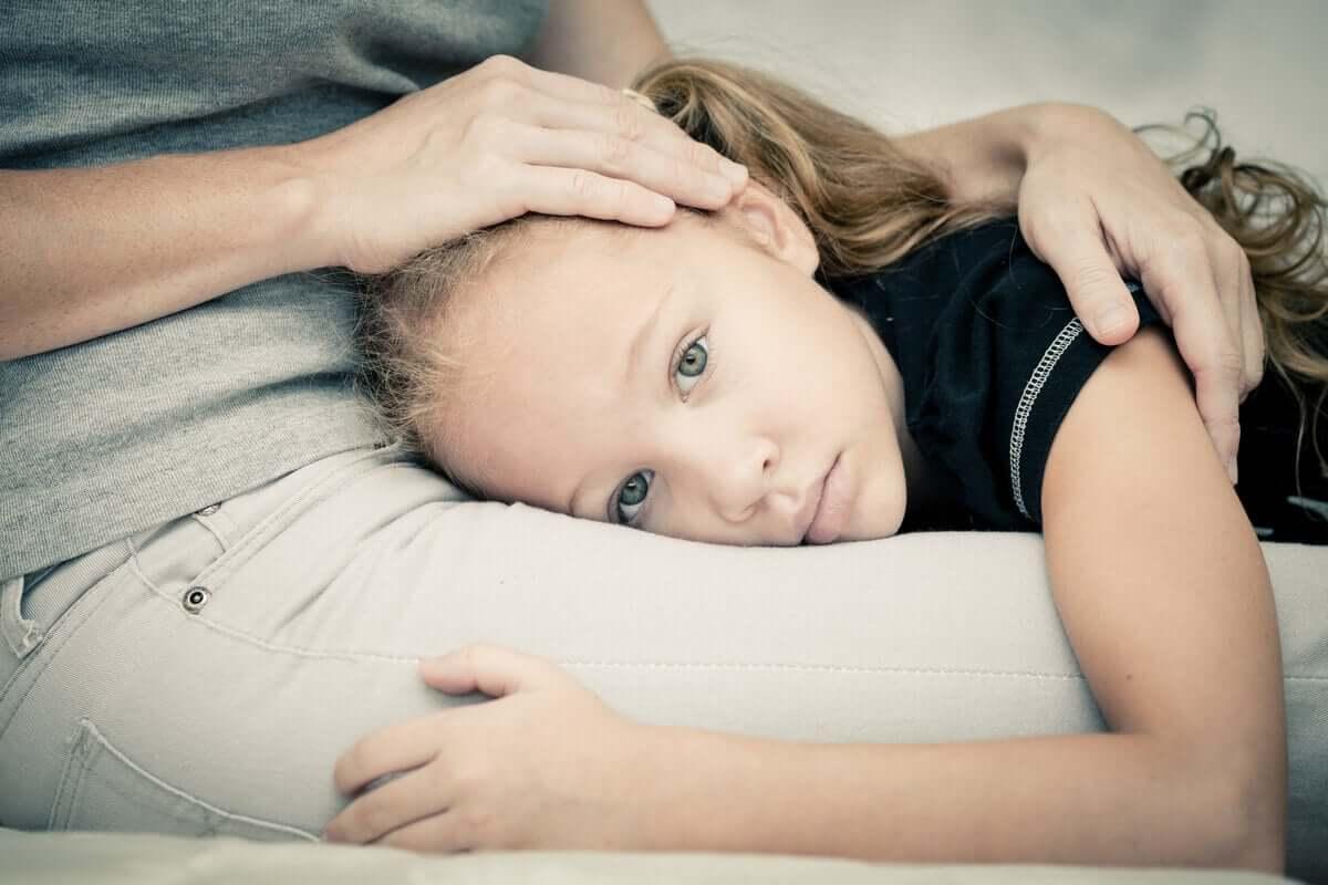 Criança com medo deitada no colo da mãe