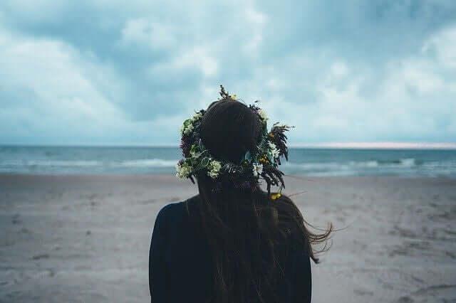 Mulher sozinha na praia em dia nublado