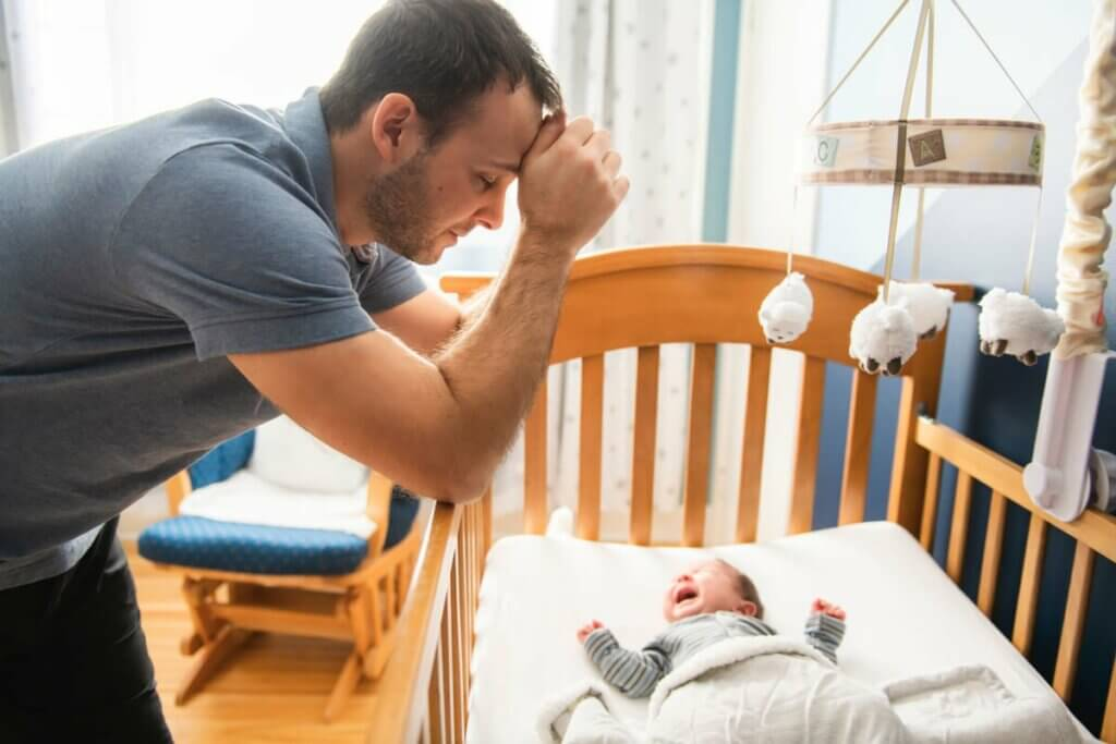 Pai com bebê chorando no berço