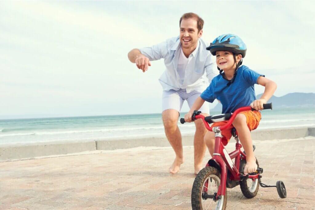 Pai e filho de bicicleta na praia