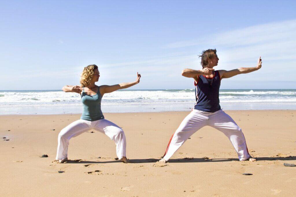 Casal praticando qi gong na praia