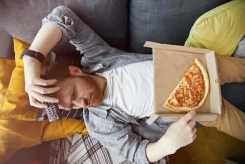 Homem comendo pizza no sofá
