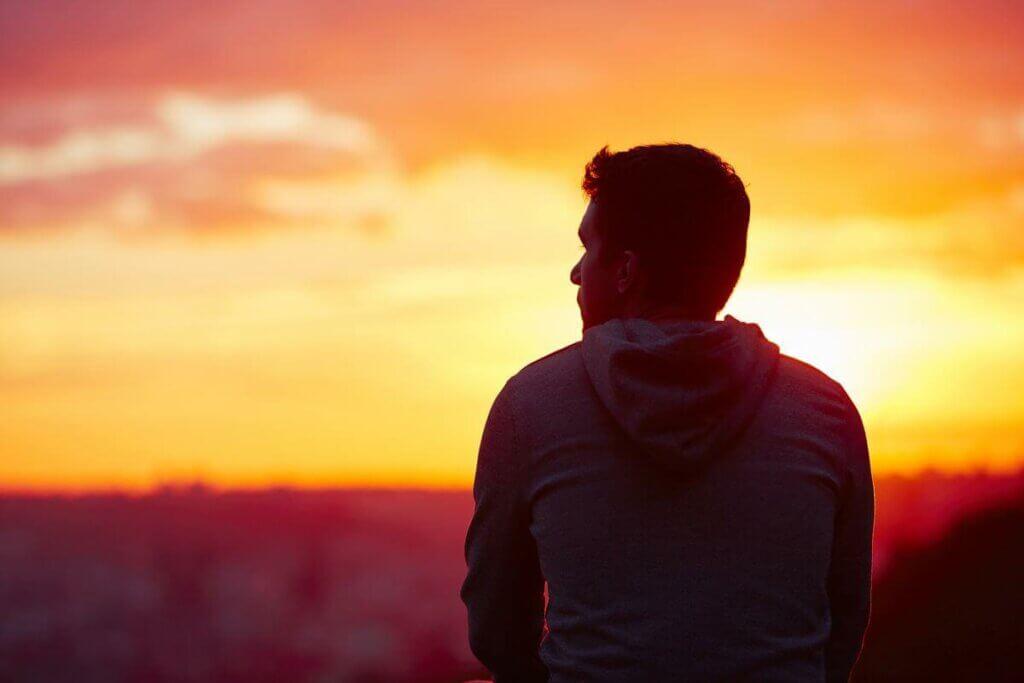 Homem observando o por do sol