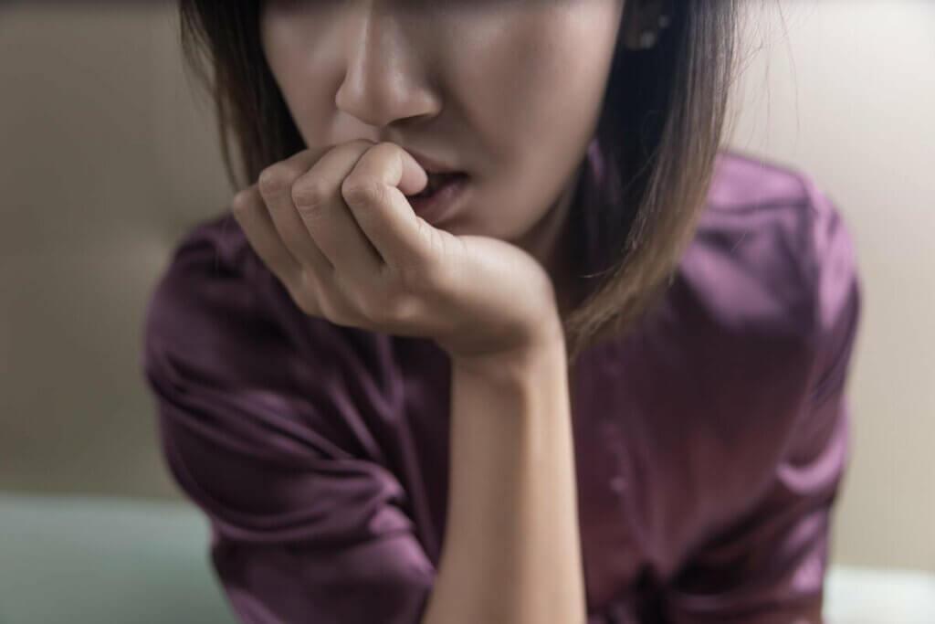Mulher ansiosa roendo as unhas