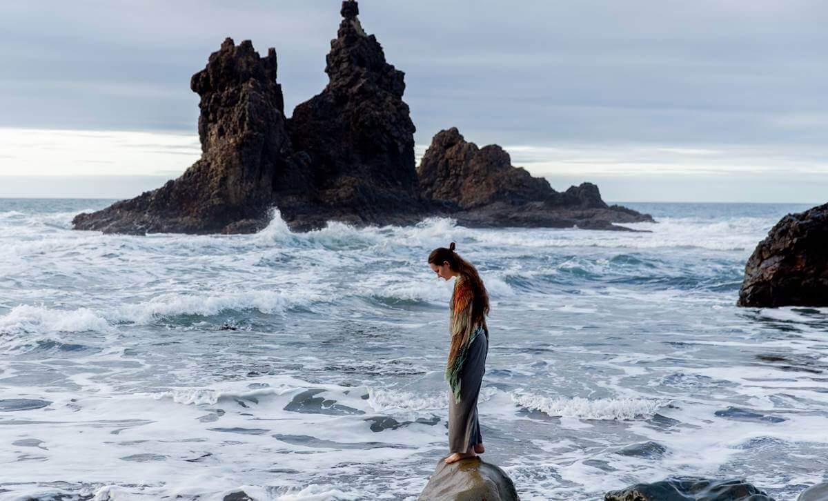 Mulher em pedra na beira do mar