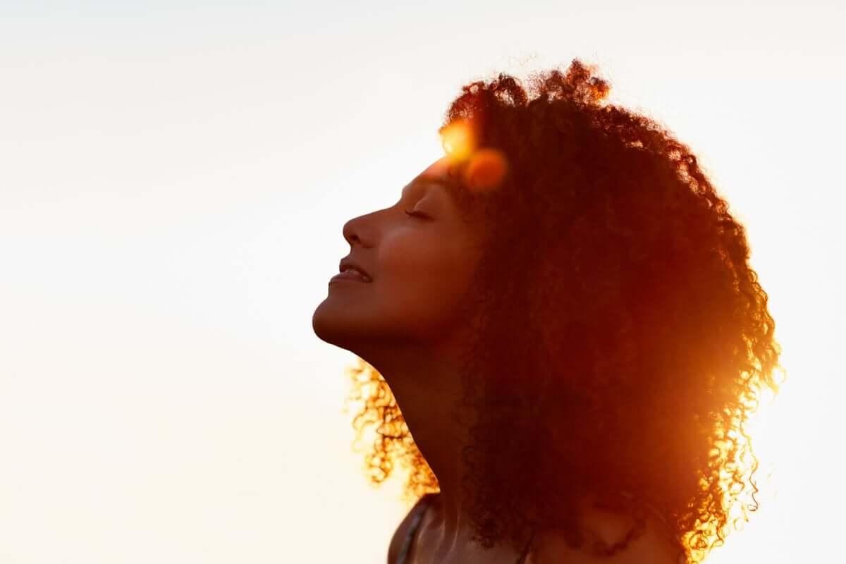 Mulher de olhos fechados diante do sol