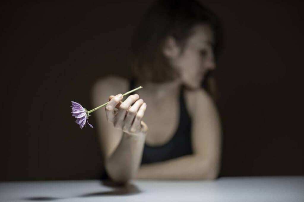 Mulher triste segurando flor