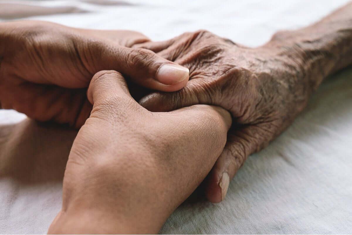 Pessoa segurando a mão de familiar doente