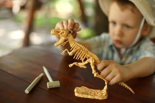 Menino brincando com dinossauro