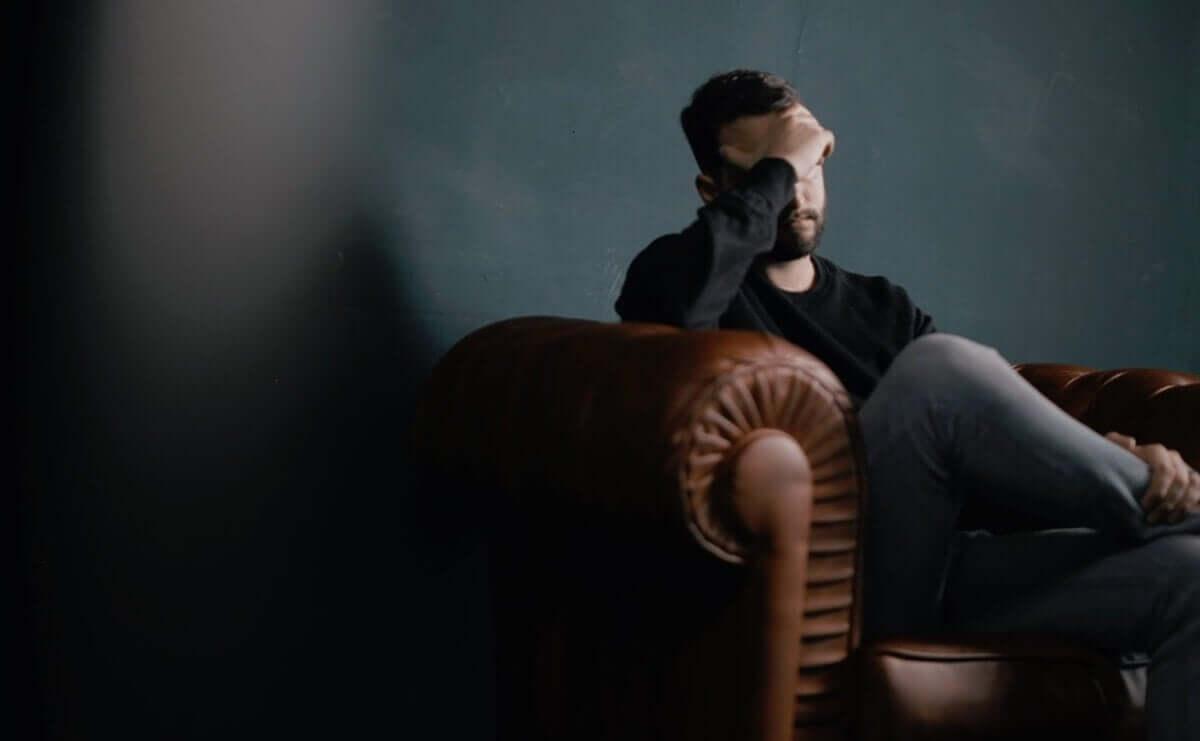 Homem preocupado no sofá