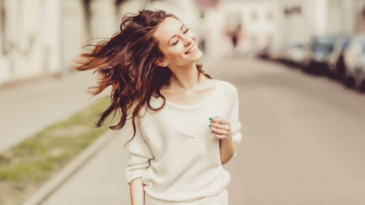 Mulher caminhando na rua feliz
