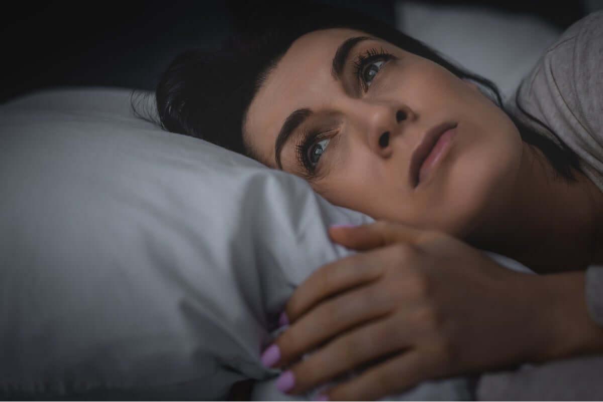 Mulher com insônia tentando dormir