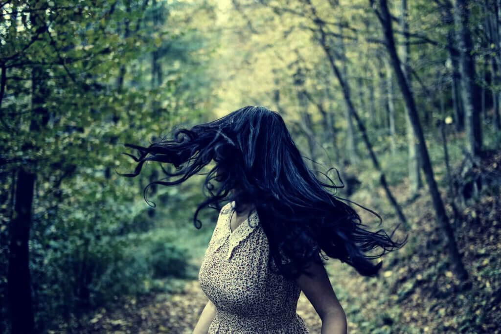 Mulher fugindo em floresta