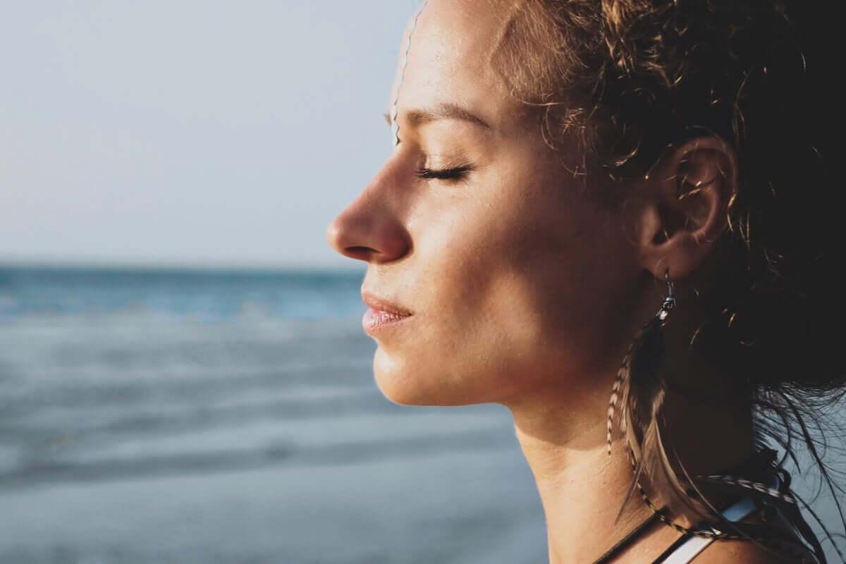 Mulher de olhos fechados na praia