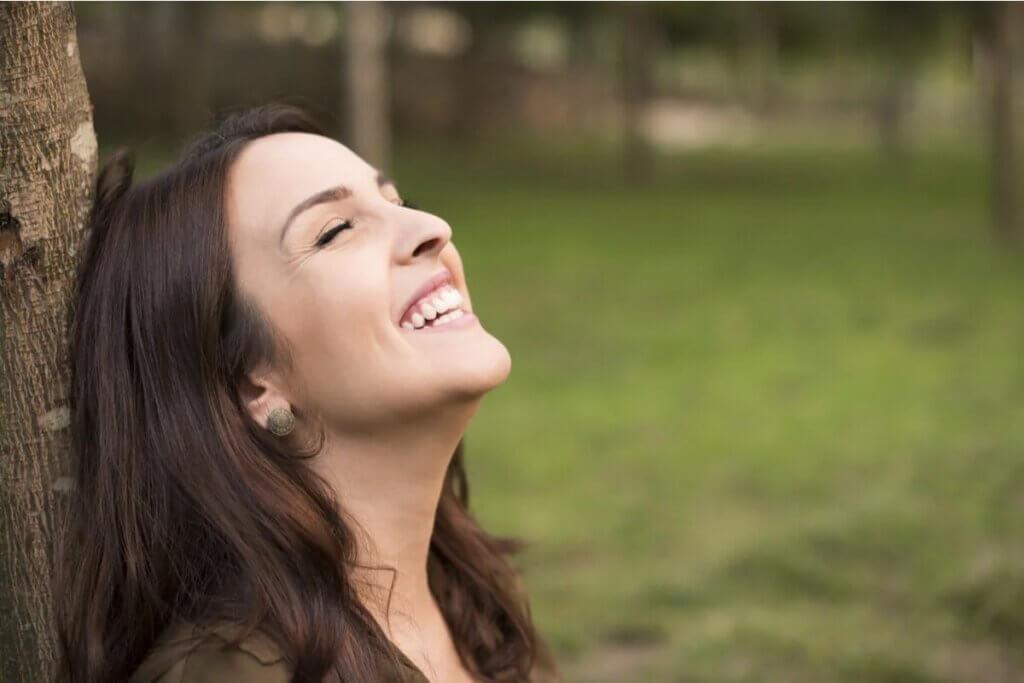 Mulher rindo ao ar livre