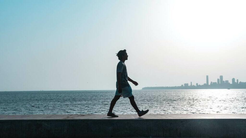 Rapaz caminhando diante do mar