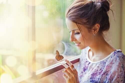 Mulher vendo borboleta na janela
