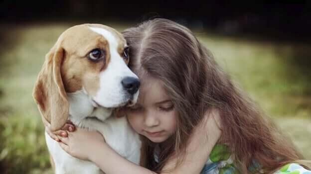 Menina abraçando cachorro