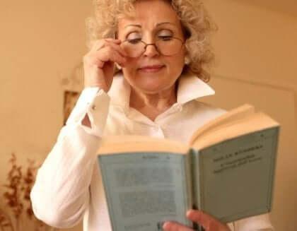 Mulher lendo livro segurando óculos