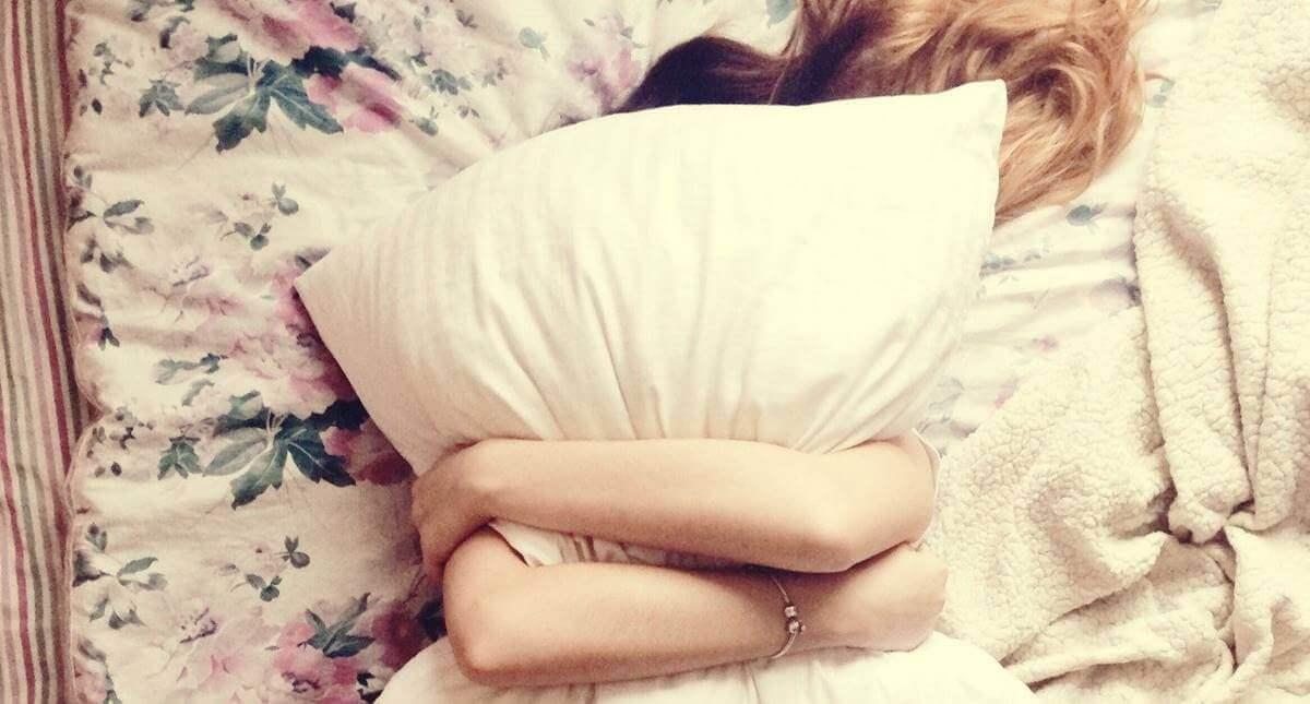 Menina abraçada com travesseiro