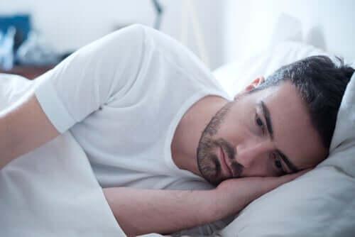 Homem triste deitado na cama