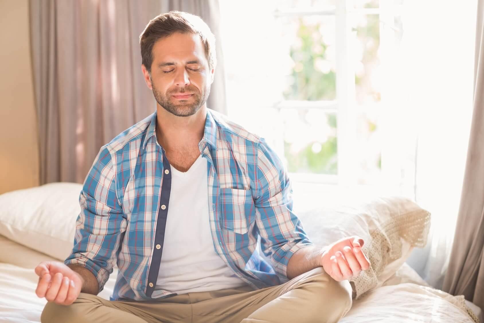 Homem meditando na cama