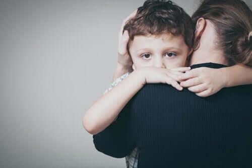 Menino abraçado com a mãe